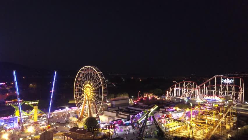 Funfair at night aerial shot pull backwards Royalty-Free Stock Footage #1018623703