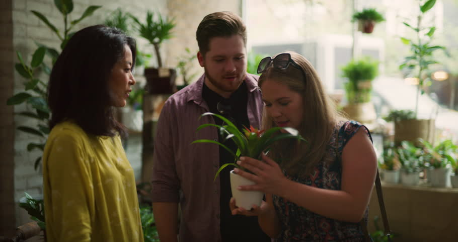 Laughing and chatting young couple looking at plants and getting help from store owner in interior boutique flower shop with soft day lighting. Medium shot on 4k RED camera.