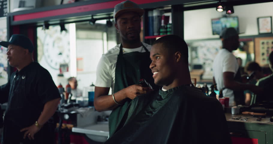 Young African American professional barber helping a customer in interior hipster barbershop with bright day lighting. Medium shot on 4k RED on a gimbal.