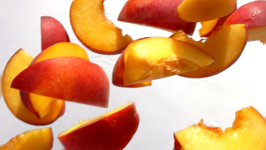 Slices of peach fly close-up on white background in slow motion