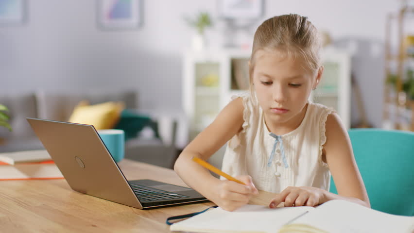 Smart Little Girl Does Homework in Her Living Room. She's Sitting at Her Desk, Uses Laptop and Writes with a Pen in Her Textbooks.