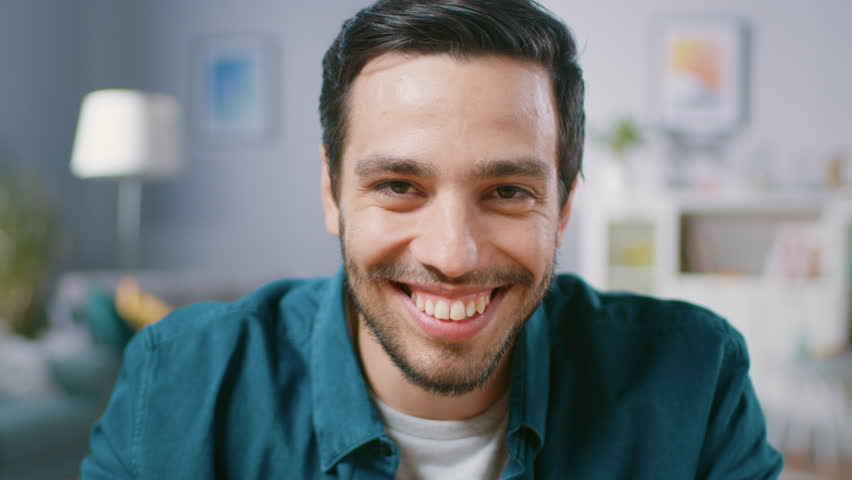 Focusing Camera Portrait of Handsome Man Sitting at Desk in His Living Room and Charmingly Smiling. | Shutterstock HD Video #1018666330