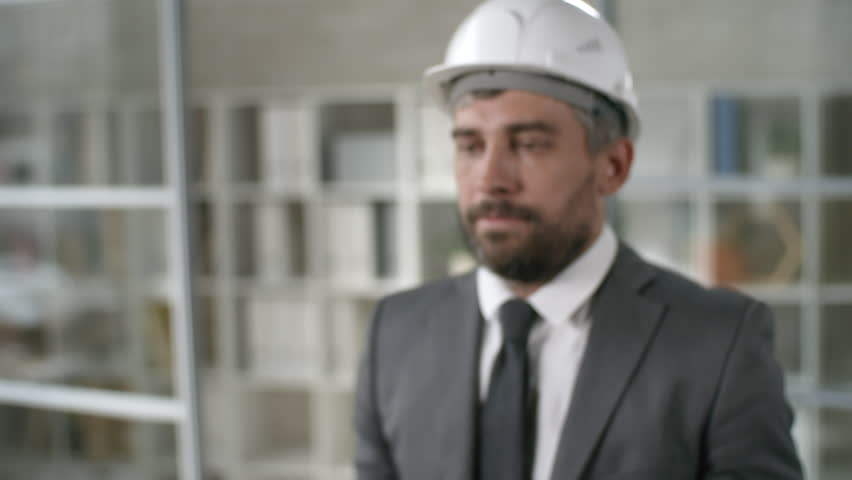 Medium shot of bearded man wearing suit and hard hat holding futuristic mobile phone. Footage suitable for adding AR graphics #1018679413