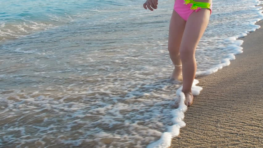 A child walks through the waves. Feet of a child on the beach. | Shutterstock HD Video #1018680853