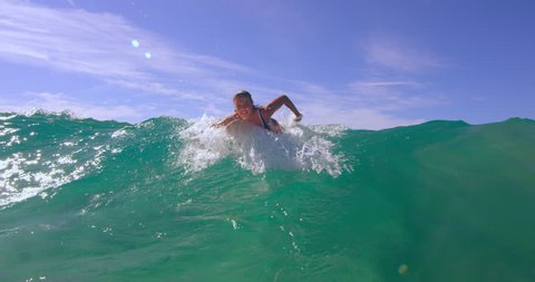 Enthusiastic blonde woman swimming with a large ocean wave on surfboard and having fun in Australian beach with bright day lighting. Wide to Medium shot on 4k RED camera.