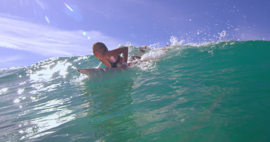Eager blonde woman swimming with a large ocean wave on surfboard and having fun in Australian beach with bright day lighting. Wide shot on 4k RED camera.