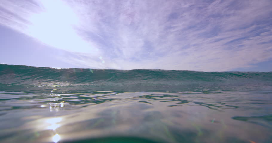 Large blue ocean wave crashing towards the camera in Australian beach with bright day lighting. Wide shot on 4k RED camera.
