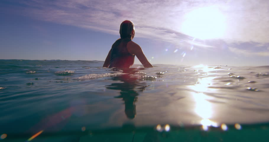Female surfer sitting on surfboard in ocean in Australian, soaking up the sun waiting for the next big wave. Use for fitness/lifestyle advertising/commercial. Medium shot on 4k RED camera.