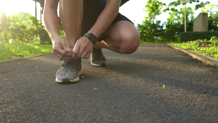 Closeup of feet of man runner getting ready tying running shoes before running in park exercising outdoors | Shutterstock HD Video #1018692874