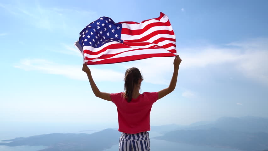 Child girl is waving American USA flag on top of mountain at sky background. Footage in slow motion #1018698124