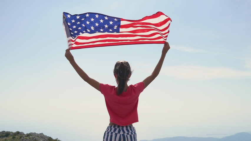 Child girl is waving American flag on top of mountain at sky background. 4K Footage #1018698994