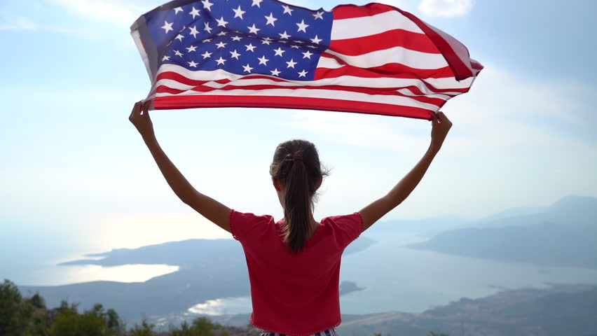 Child girl is waving American flag on top of mountain at sky background. Footage in slow motion #1018698997