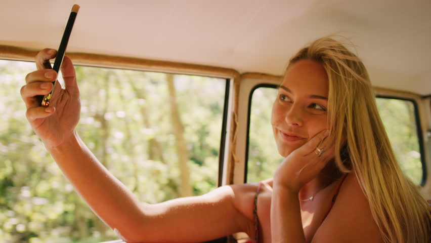 Attractive woman using mobile and takes selfies in backseat of a vintage car in the summer, in Australia in bright daylight.
