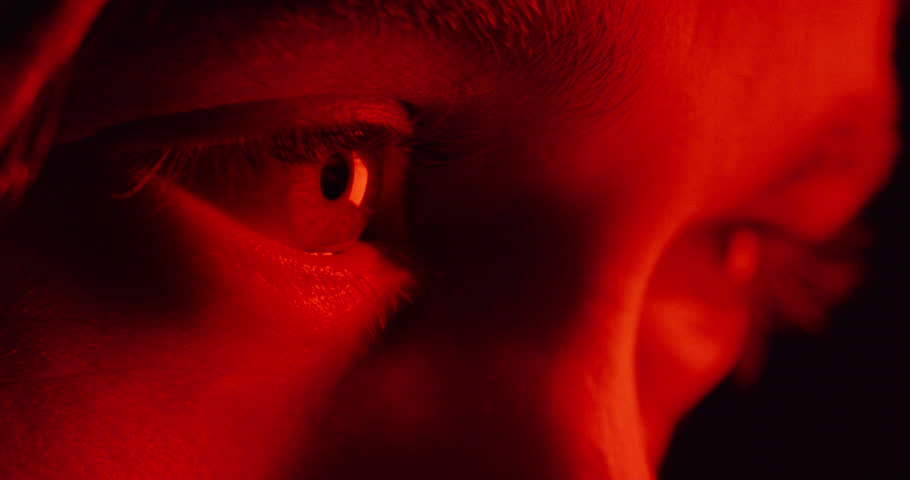 Close up macro eyes witness watching crime scene investigation colorful police lights flashing on young man suspect macro