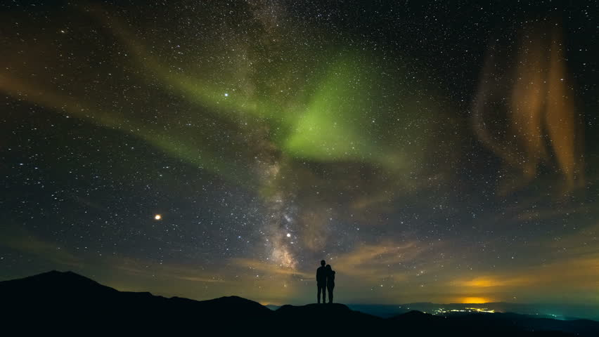The couple standing on a background of a city with a northern light. time lapse #1018717855