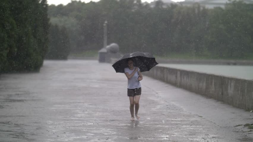Happy girl under the umbrella enjoying in the rain, heavy rain, slow motion, outdoors | Shutterstock HD Video #1018718551