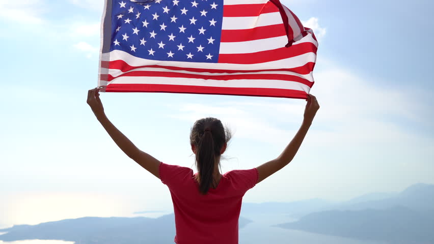 Child girl is waving American USA flag on top of mountain at sky background. 4K #1018732291
