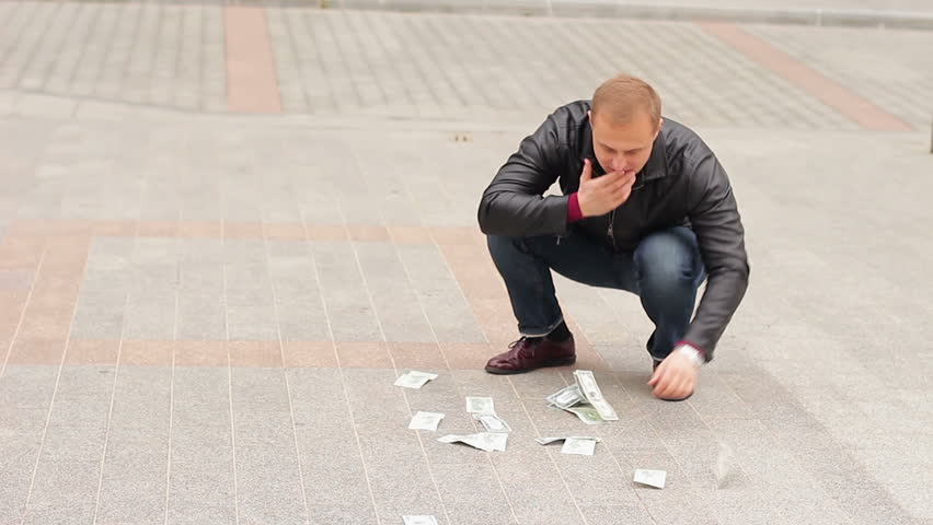 A man quickly picking up dollar bills from the floor. Concept of greed and greed #1018734772