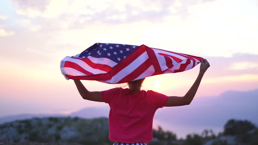 Child girl is running with USA American flag at sunset. Slow motion #1018739722