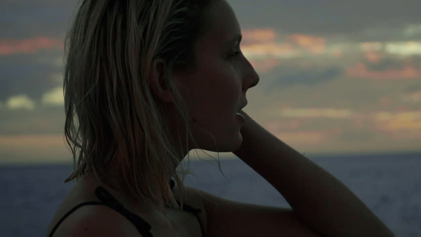 SLOW MOTION: Close up shot of a young blonde woman dancing and looking at the sunset - sunrise from a boat in the middle of an ocean - sea. Summer Vacation in Middle America.