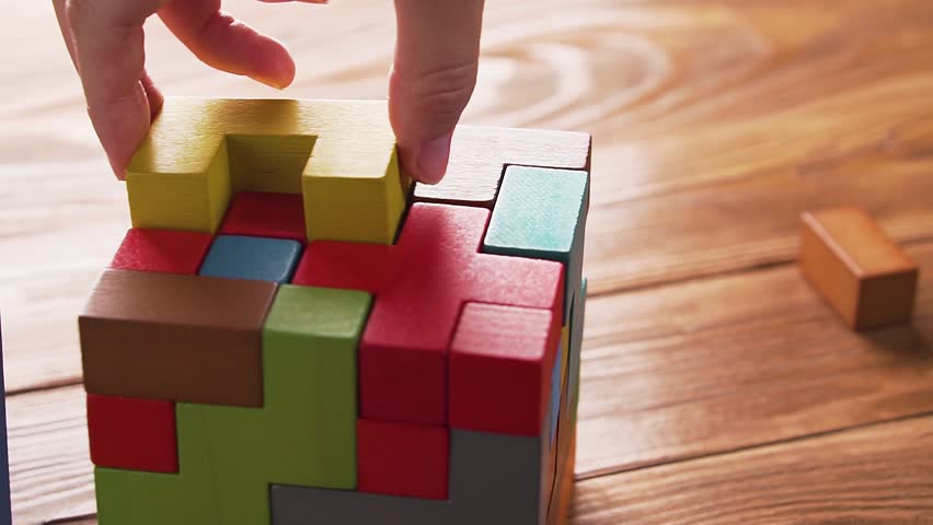 Hand folds colorful wooden cube puzzle on the brown table background, close up, dolly shot. Concept of decision making process, logical thinking. Geometric shapes on a wooden background.   | Shutterstock HD Video #1018750456