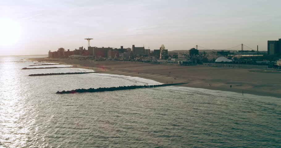 Aerial view of the shoreline of Coney Island at dusk, New York City, with soft natural lighting. Wide shot on 4k RED camera