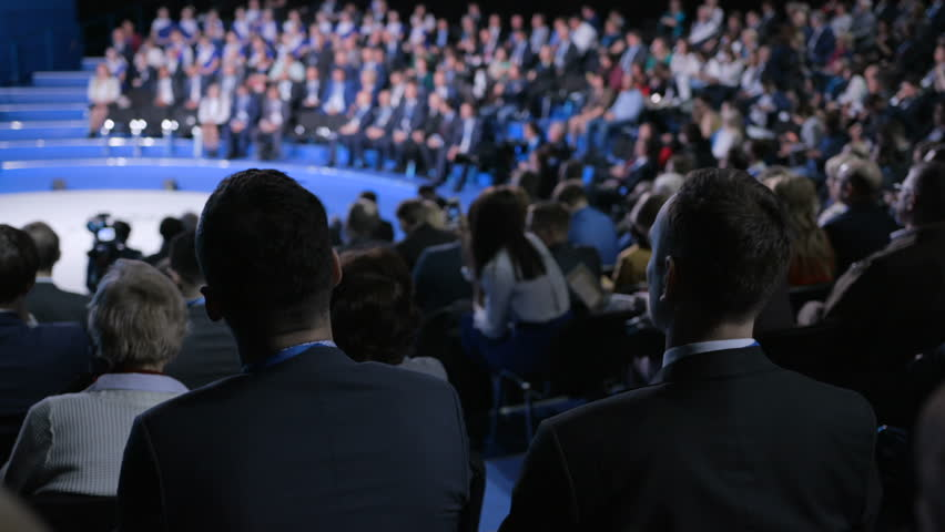 Male entrepreneur at crowded forum for banking leadership or trading collaboration. Information concept for development idea of sale indoors. Row of seats in large place for worker expert or spectator | Shutterstock HD Video #1018757332