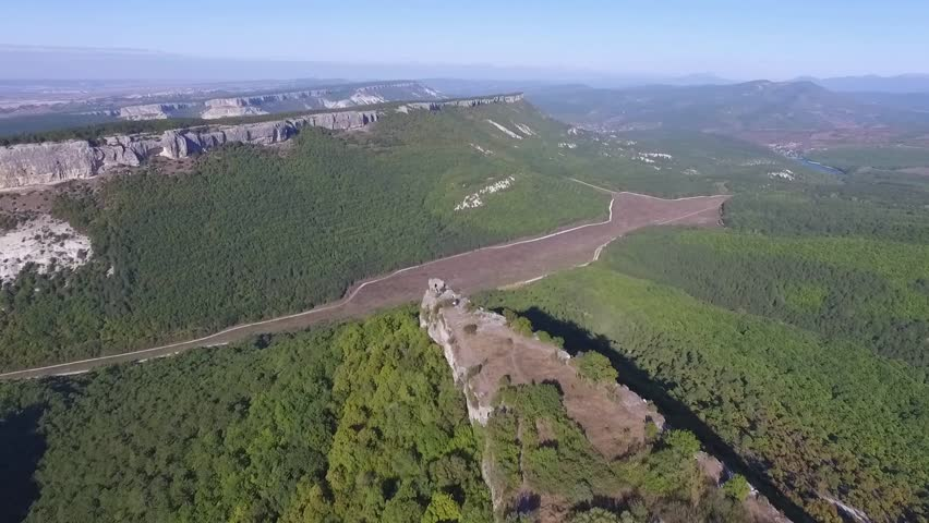Altai mountains removed from the drone. Shot. Aerial view to landscape of green valley flooded with light with lush green grass, covered with stone, summer day under a blue sky with Altai mountains