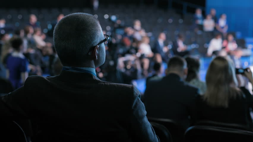 Official team works at crowded forum for collaboration or trading education. Modern concept of economic briefing for male partner or politician. Row of seats in large place for job worker or spectator | Shutterstock HD Video #1018763074