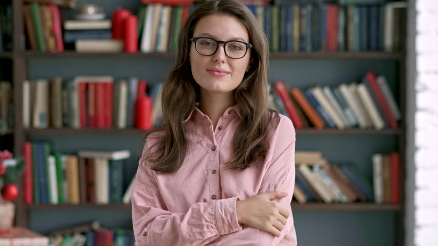Close up portrait of young pretty librarian woman smiling happy looking at camera in library bookshelf background knowledge learning