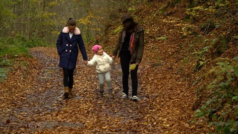 A young mother with her two children walks through the autumn forest. They walk along the forest path. They are happy.
