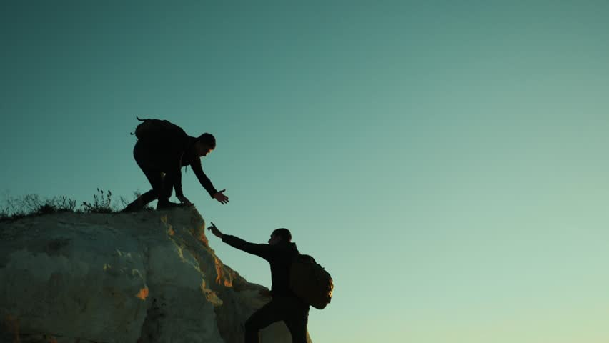 Silhouette hiker man tourists hands help climber climbs a mountain. walking tourist hiking adventure climbers sunset climb the mountain . slow motion video. hiker sunlight on top win victory the hill | Shutterstock HD Video #1018815049