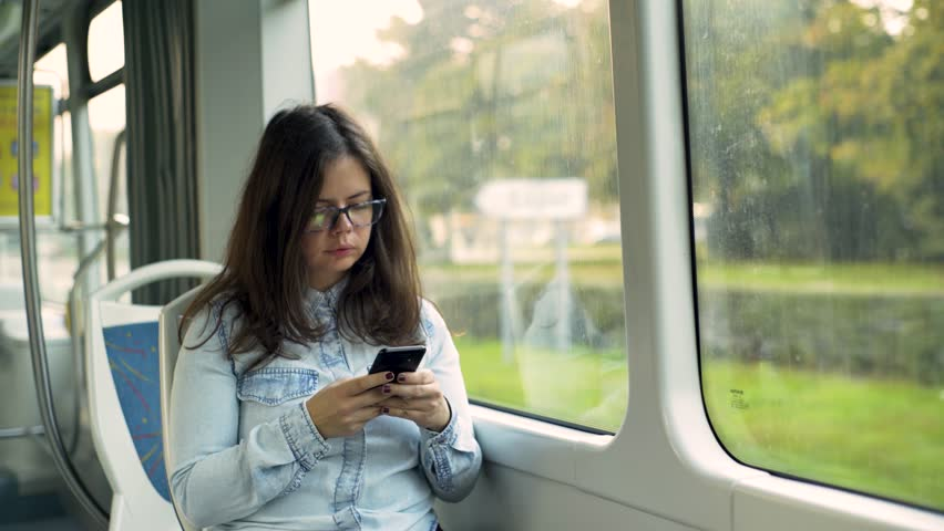 Young girl addictive to a cell phone typing in the tram. #1018821001