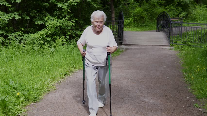 Grandma walks in the park with sticks for Nordic walking in retirement
