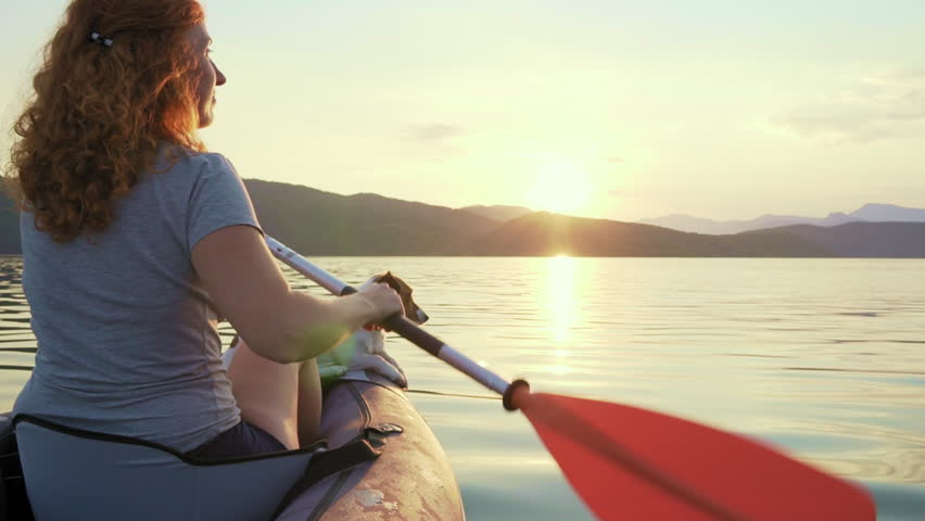 Happy young woman with her dog Jack Russell Terrier slow motion slide paddling on an inflatable kayak on water of large mountain lake against beautiful orange sunset. Family Sports Weekend. Lifestyle