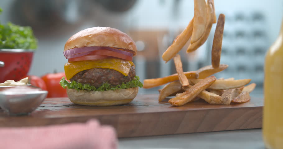 Delicious hamburger and salty fries falling onto a wooden board on a table with bright studio lighting. Close up slow motion shot on 4k phantom flex.