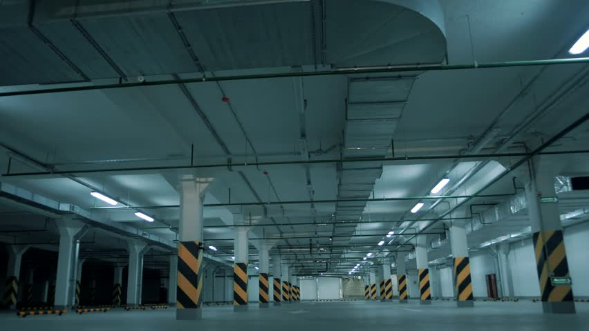 Fluorescent lights flicker and light up and illuminate a large underground parking