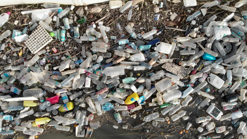 Spain - October 28, 2018: Aerial drone video waterfront scrap-heap pile of garbage. Above view plastic bottles rubbish pollution marine debris on lake shore Global damage environmental dumping concept