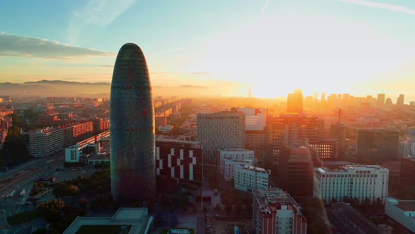 Barcelona, Spain - May 28, 2018: Torre Glories or Torre Agbar as the landmark skyscraper sunrise view from air. Barcelona is the second most populous municipality of Spain. Royalty-Free Stock Footage #1018867948