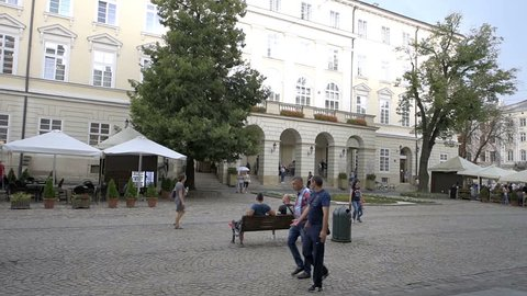 Lviv, Ukraine - July 31, 2018: Historic Ukrainian Polish city in old town market square park, people walking by benches on cobblestone street, windy day weather