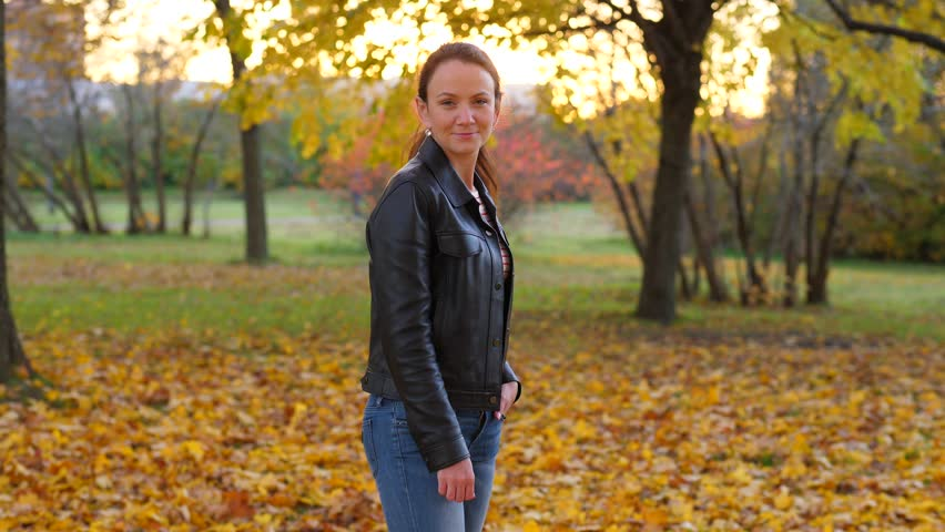 Elegant pretty young woman portrait at autumn, she look straight to camera then turn eyes away. Lady wear black jacket and jeans. Blurred background | Shutterstock HD Video #1018879414