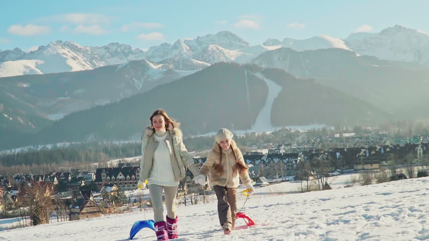 Mother and child girl holds in hands sleds are go against mountains at camera. Zooming | Shutterstock HD Video #1018895530