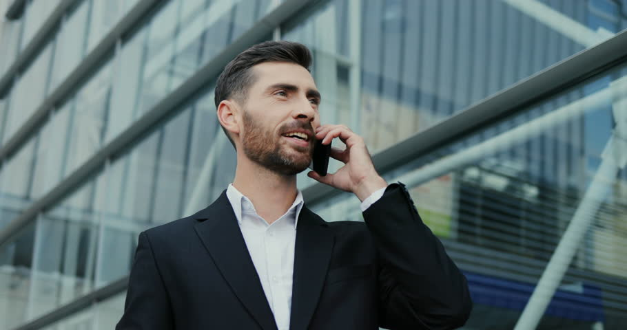 Portrait of the handsome smiled Caucasian businessman talking on the phone cheerfully and doing yes gesture with a hand. Close up. Outdoor. #1018904473
