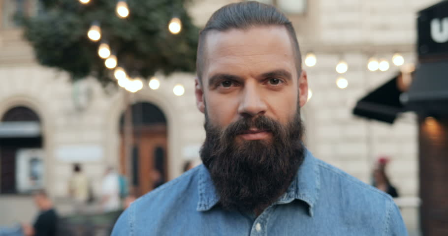 Portrait of the handsome Caucasian young man with long beard and in jeans blue shirt standing on the street of a town with lights and looking with shrewd eyes straight to the camera. Close up. Outdoor