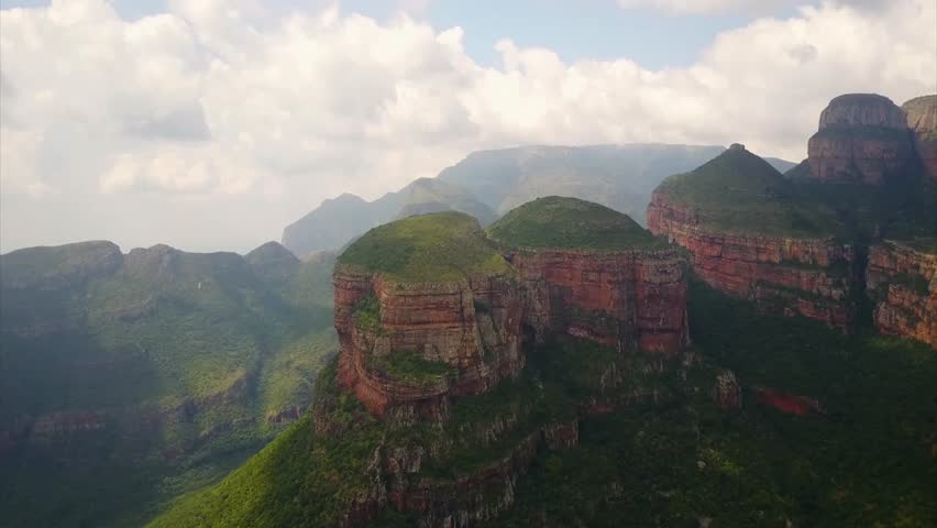 Drone shot of Blyde River Canyon covered with lush, mountains in background, South Africa | Shutterstock HD Video #1018925071