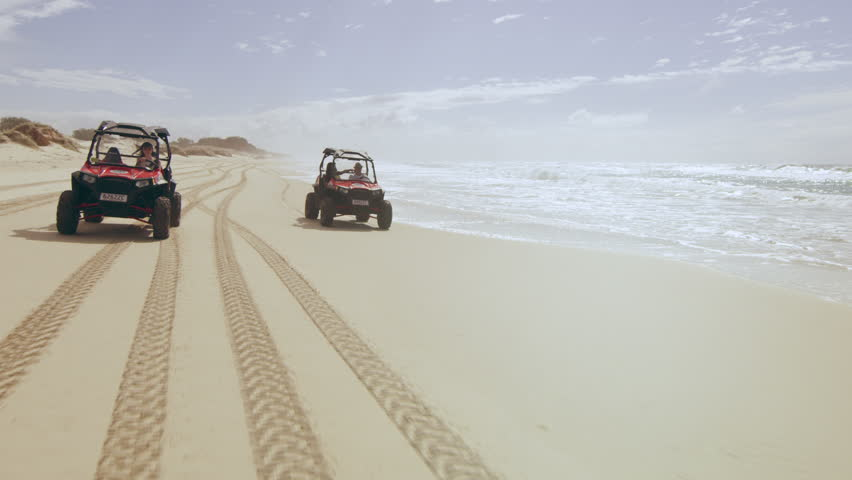 Two ATV vehicles racing on a beautiful beach with ocean and open sky in the background in Australia. Wide angle on 4k RED camera.