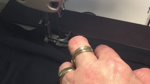 Seamstress sews a garment close up  from above with industrial sewing machine needle running along new seam.