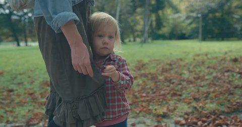 A little toddler is in the park with his mother on an autumn day