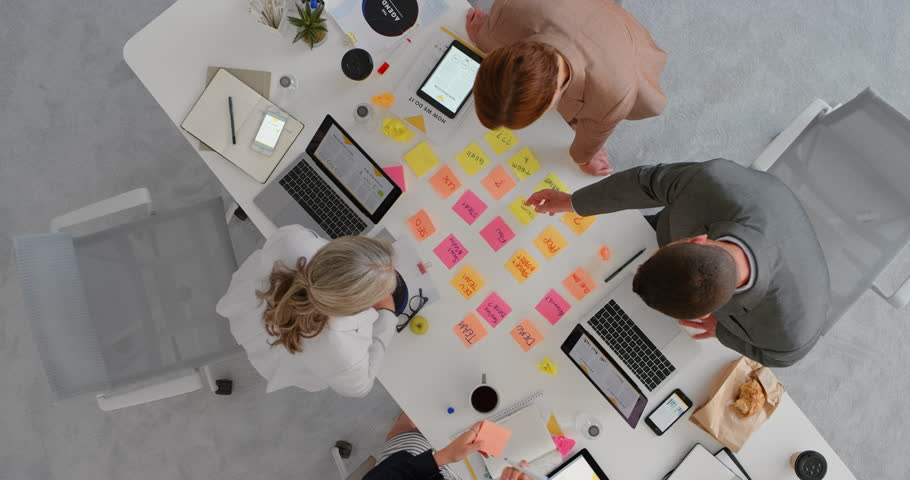 group of multi ethnic business people working together brainstorming strategy for innovative company making notes using colorful paper in boardroom meeting top view
