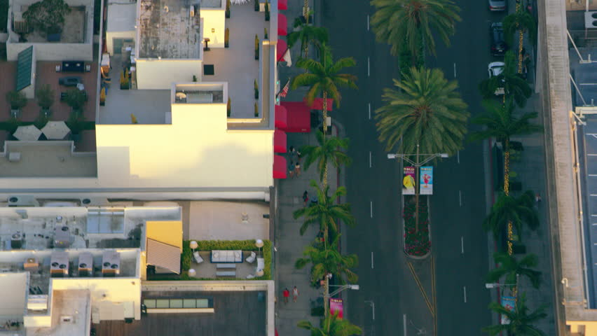 Flying over Rodeo Drive in Los Angeles and palm trees while sun sets. Medium close shot with a RED camera.